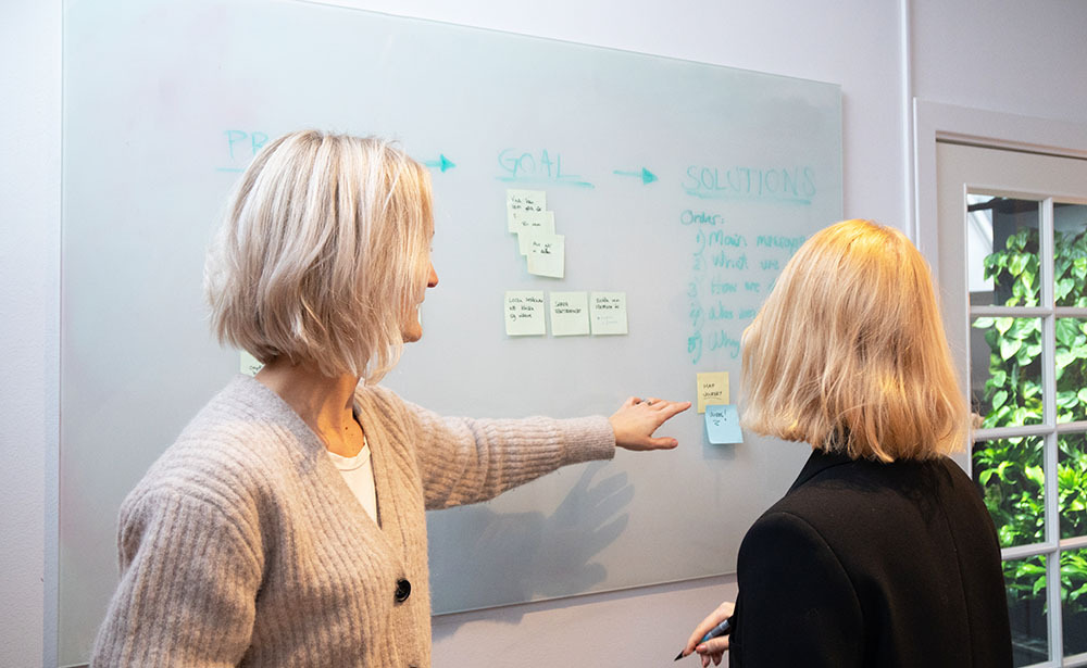 UX designers pointing to post-it note on whiteboard planning website experience