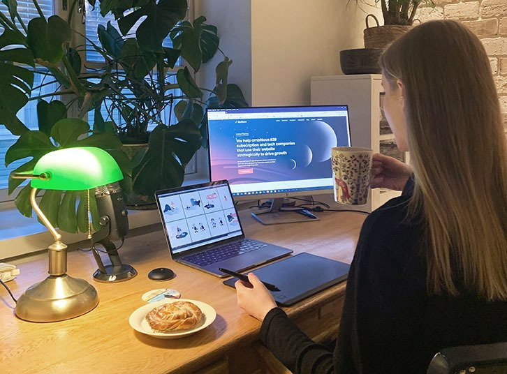 Designer sitting at desk working on two screens
